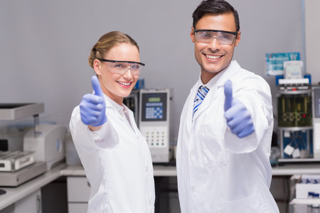 Smiling scientists looking at camera thumbs up in laboratory