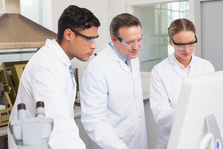 attentively: Scientists working attentively with computer in laboratory
