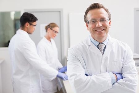 Científico sonriente mirando a la cámara mientras sus colegas de trabajo detrás en el laboratorio