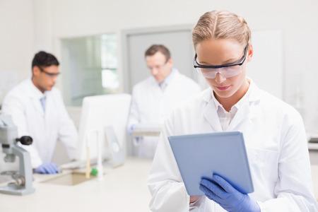 Científico que usa la tableta, mientras que sus colegas de trabajo detrás en el laboratorio