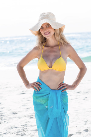 escapism: Smiling pretty blonde posing with sarong and straw hat at the beach