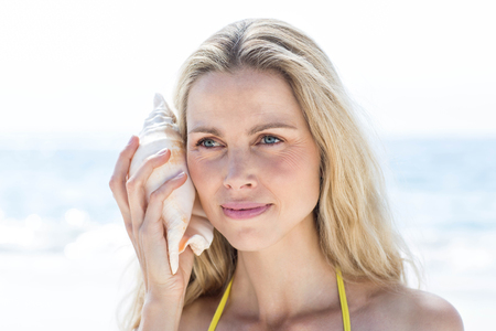 fair woman: Smiling pretty blonde listening the seashell at the beach