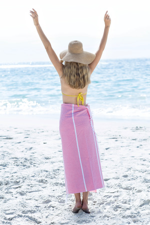 fair woman: Happy blonde standing by the sea arms raised at the beach