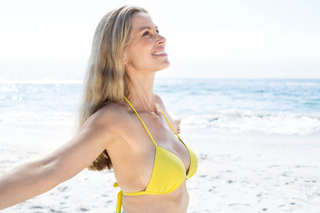 fair woman: Smiling pretty blonde standing by the sea arms outstretched at the beach Stock Photo