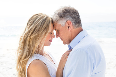 mid adult couple: Happy couple standing by the sea and hugging each other at the beach Stock Photo