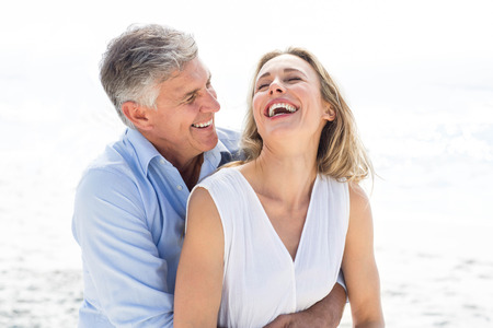 man woman hugging: Happy couple laughing together at the beach