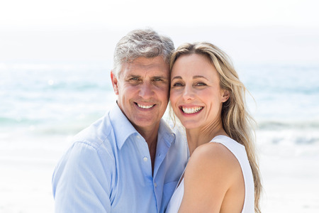 Happy couple standing by the sea and smiling at camera at the beach