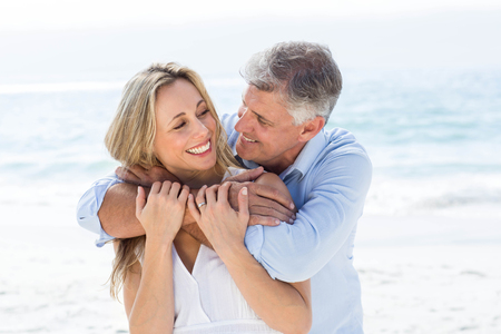 mid adult couple: Happy couple hugging each other by the sea at the beach Stock Photo