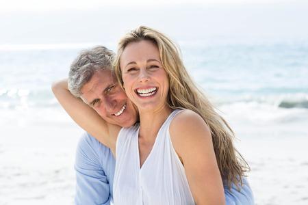 riendo: Pareja feliz riendo juntos en la playa