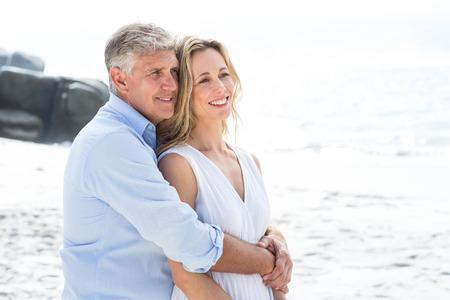 parejas felices: Feliz pareja de pie junto al mar en la playa