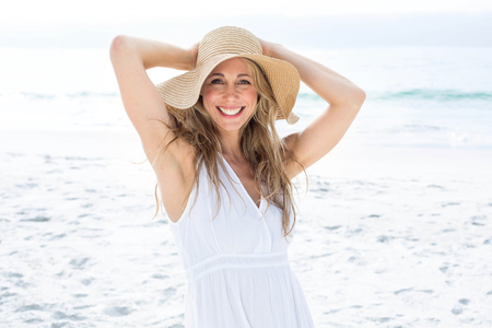 vestido blanco: Smiling blonde in white dress looking at camera and wearing straw hat at the beach