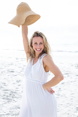 vestido blanco: Smiling blonde in white dress looking at camera and holding straw hat at the beach