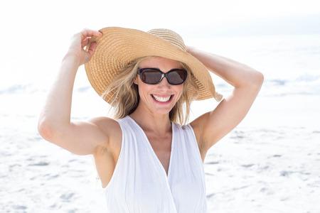 gente adulta: Sonriente rubia de vestido blanco que llevaba gafas de sol y sombrero de paja en la playa Foto de archivo