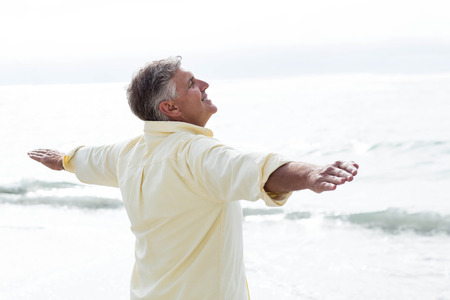 escapism: Smiling man standing by the sea arms outstretched at the beach Stock Photo