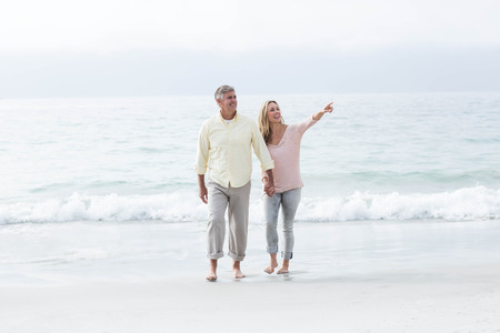 Happy couple walking by the sea at the beach photo