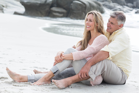 man woman hugging: Happy couple sitting on the sand at the beach