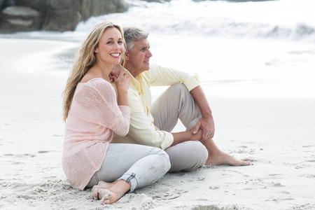 parejas felices: Feliz pareja sentada en la arena en la playa Foto de archivo