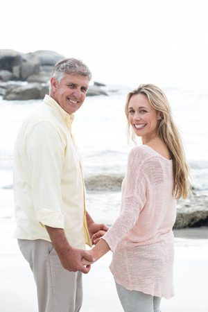 Happy couple holding hands and smiling at camera at the beach