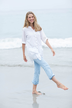 escapism: Smiling blonde walking by the sea and looking at camera at the beach
