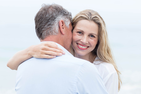 fair woman: Happy couple hugging each other by the sea at the beach Stock Photo