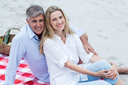 mature women: Happy couple sitting on a blanket and hugging each other at the beach