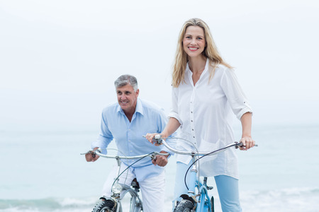 woman bike: Happy couple cycling together at the beach Stock Photo