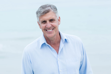 guy portrait: Smiling man looking at camera at the beach