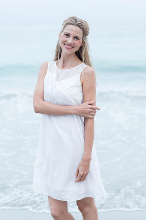 mature women: Smiling blonde in white dress looking at camera at the beach Stock Photo