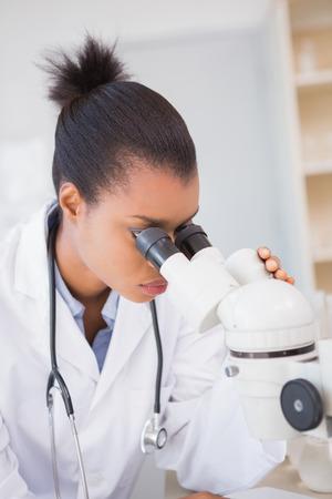biochemist: Scientist looking in microscope in laboratory Stock Photo