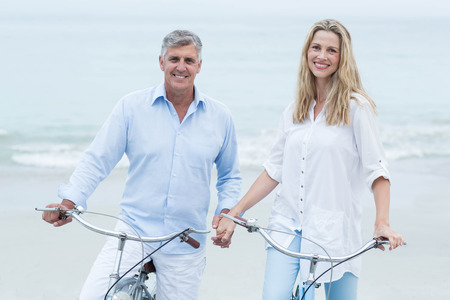 Happy couple cycling together at the beach Foto de archivo