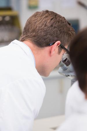biochemist: Scientist looking through a microscope in laboratory Stock Photo