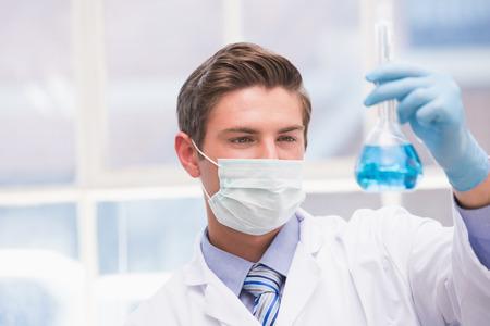 biochemist: Scientist examining beaker with blue fluid in laboratory
