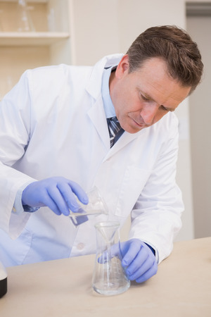 precipitate: Scientist doing experimentations in flask in the laboratory