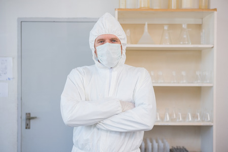 protective suit: Scientist in protective suit looking at camera with arms crossed in the laboratory