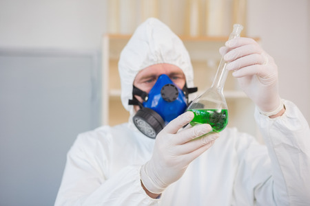 precipitate: Scientist in protective suit examining green precipitate in the laboratory
