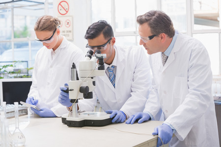 scientist man: Scientists examining something with the microscope in the laboratory
