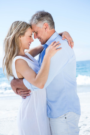 escapism: Happy couple standing by the sea and hugging each other at the beach Stock Photo
