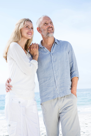 beach blond hair: Happy couple hugging each other at the beach