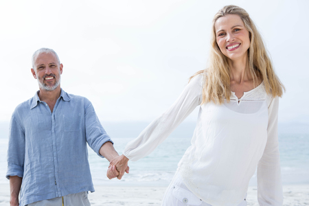 attractive female: Happy couple holding hands at the beach