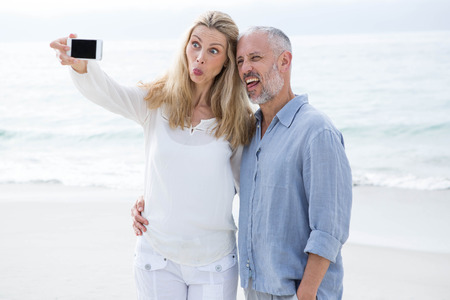 Happy couple taking selfie with mobile phone at the beach