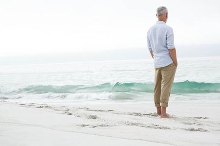 hombres maduros: Hombre pensativo que se coloca al lado del mar en la playa