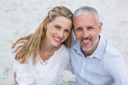 mujeres maduras: Feliz pareja sentada en la arena y mirando a la c�mara en la playa Foto de archivo