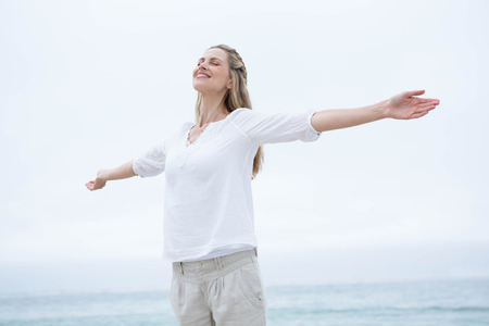 outdoors woman: Smiling pretty blonde standing by the sea arms outstretched at the beach Stock Photo