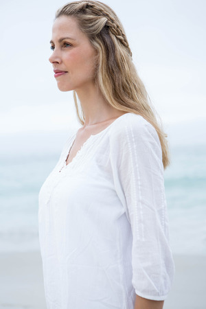 fair woman: Smiling blonde standing by the sea at the beach
