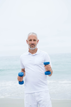 body concern: Fit man lifting dumbbells at the beach