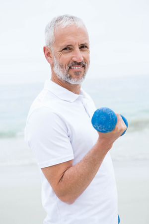 Fit man lifting dumbbells at the beach
