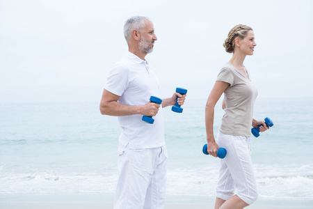 body concern: Fit couple lifting dumbbells at the beach Stock Photo