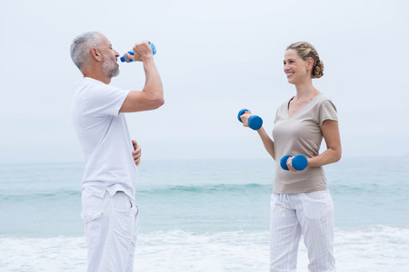 man drinking water: Fit couple doing sport at the beach Stock Photo