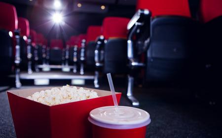 cine: Filas vacías de asientos de color rojo con palomitas de maíz y bebidas en el piso en el cine Foto de archivo