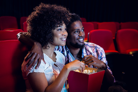 Happy young couple watching a film at the cinema Stock Photo